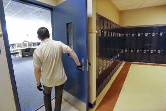 A school janitor opens the door to a staff room inside Bothell High School, in the Northshore school district in Bothell, Wash.