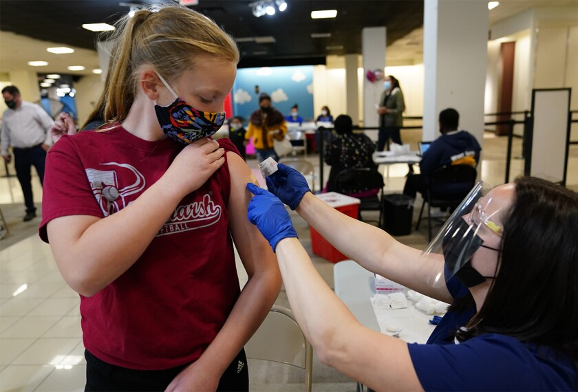 13-year-old Olivia Edwards gets a bandage from a nurse after receiving the Pfizer COVID-19 vaccine at a vaccination clinic in King of Prussia, Pa. on May 11, 2021.